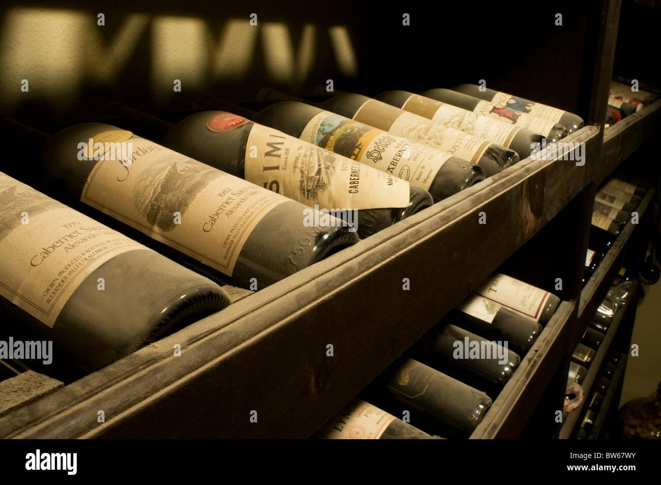 Old vintage dusty wine bottles resting in wine cellar for Old wine rack