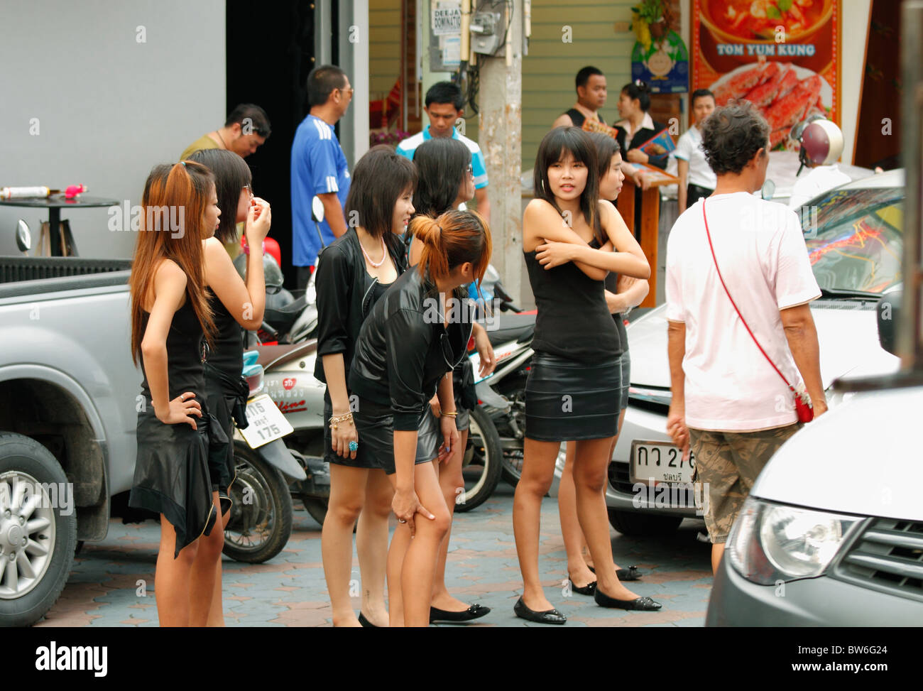 Black color dressed young Thai girls calling customers in in the front of a bar - night club Pattaya Thailand October 2010 & Black color dressed young Thai girls calling customers in in the ...