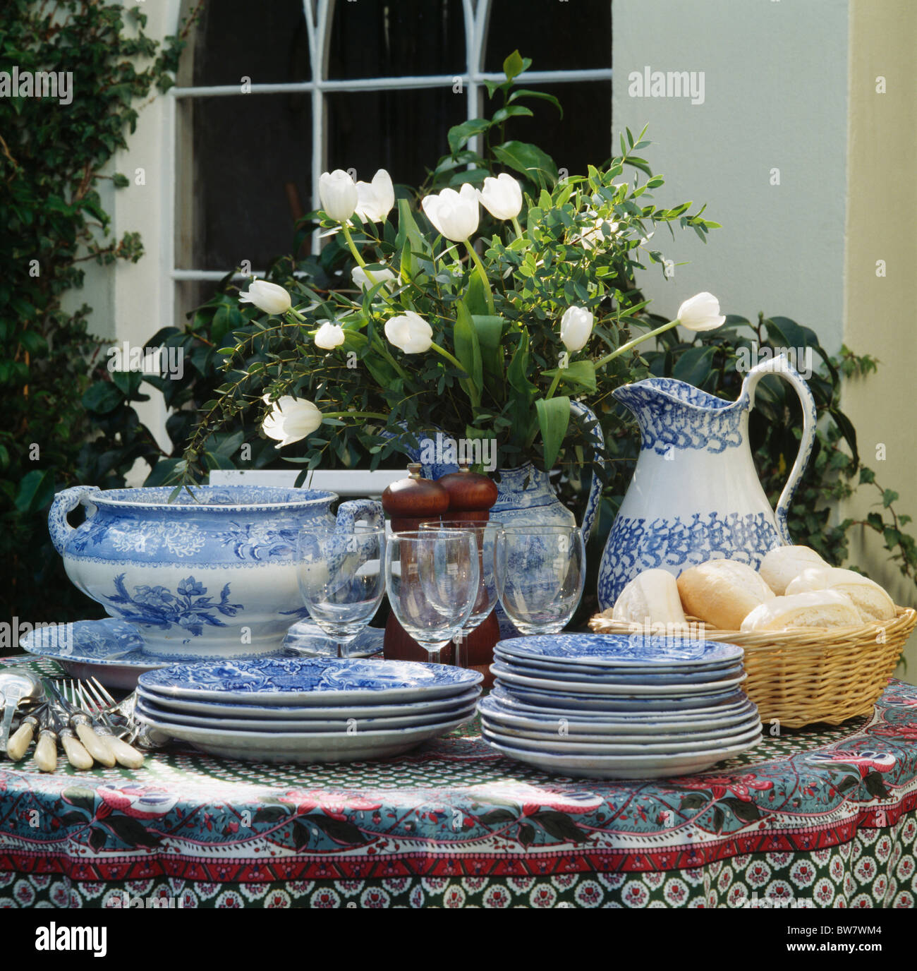 Close up of bluewhite antique china and vase of white tulips on close up of bluewhite antique china and vase of white tulips on garden table in front of window reviewsmspy