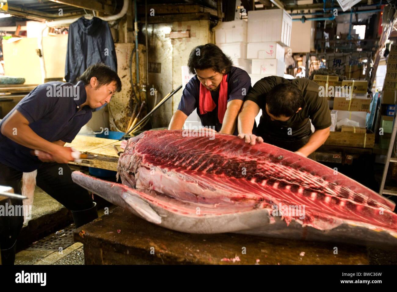 Men cutting a tuna fish at tsukiji fish market tokyo for Japan fish market