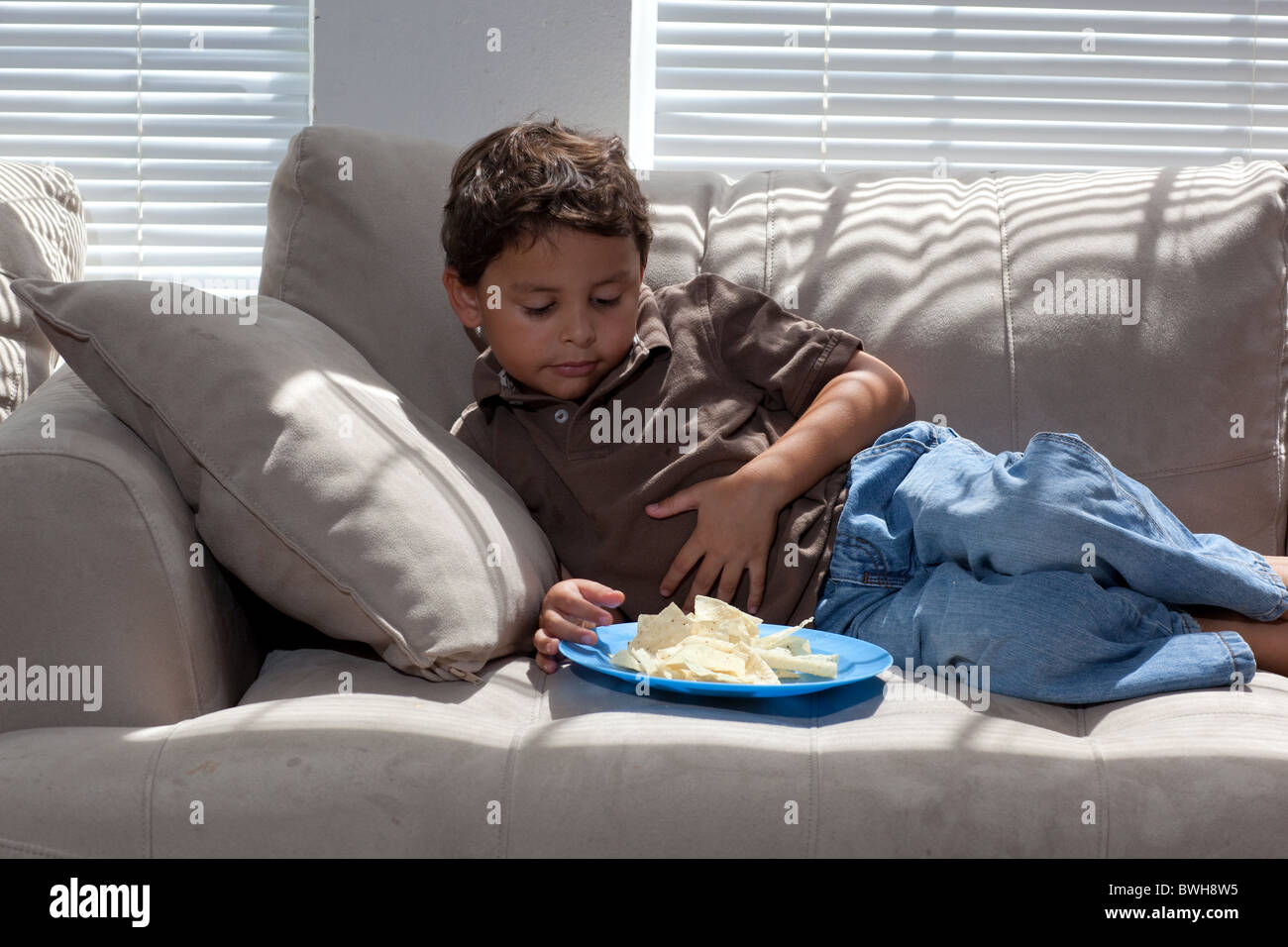 four year old mexican american boy eats potato chips for a snack on stock photo royalty free. Black Bedroom Furniture Sets. Home Design Ideas