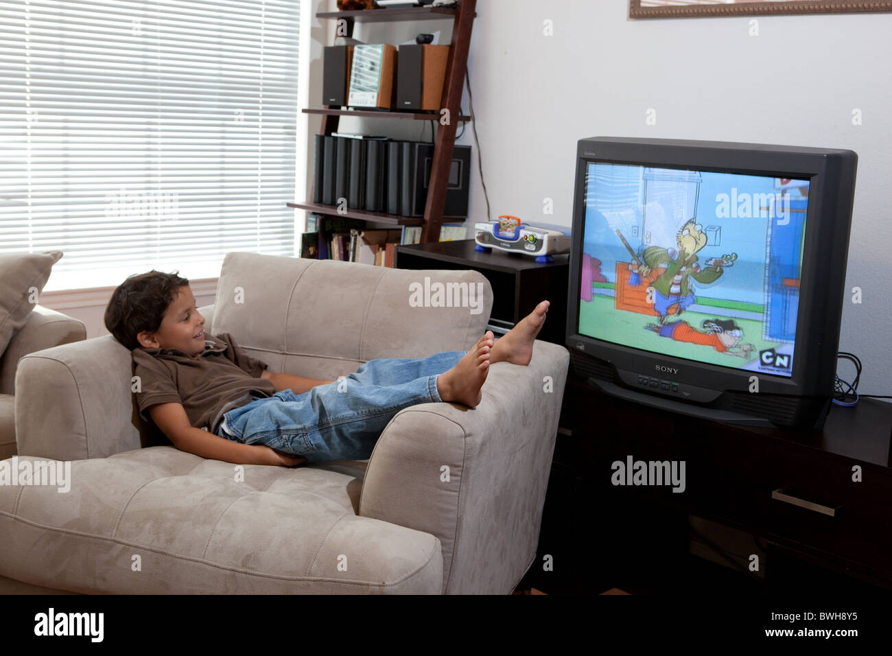 Four-year-old Mexican-American boy lounges in armchair ...