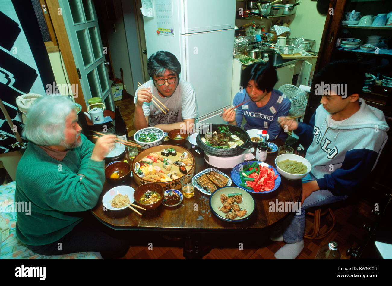 Japanese Family Eating Meal Together At Kitchen Table In