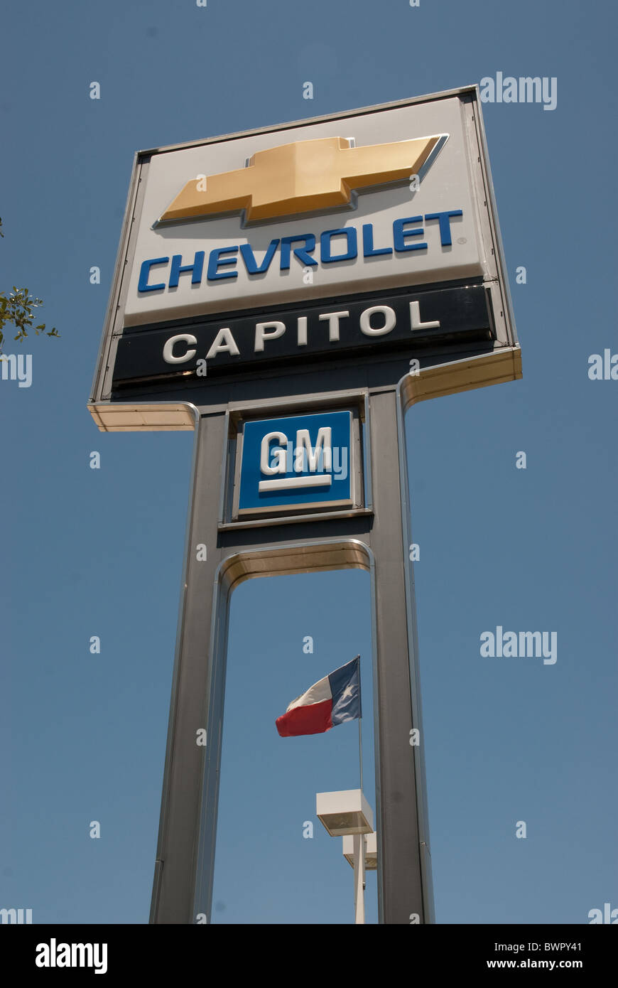 Large capital chevrolet sign on standards shows chevy and general motors logos in front of dealership in austin