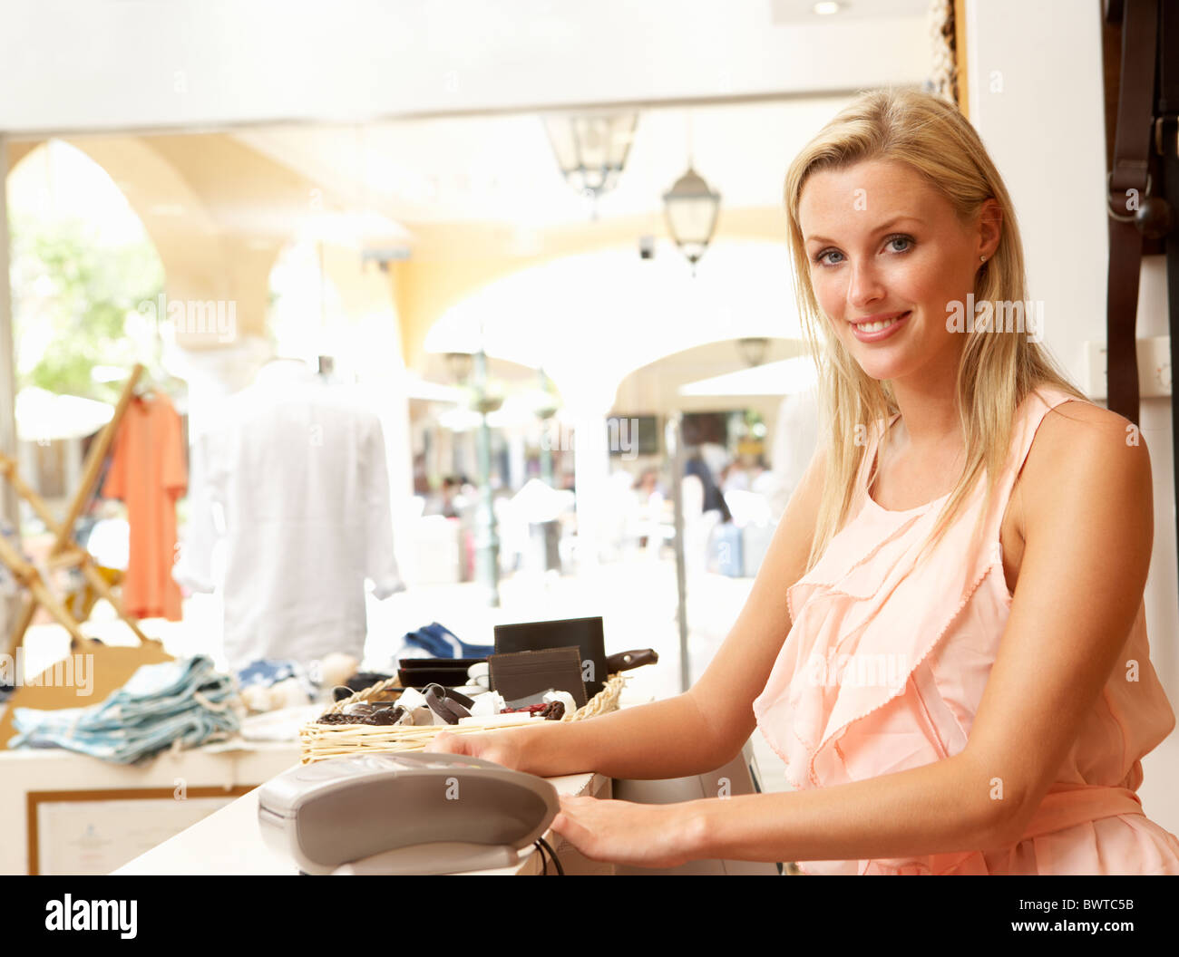 s assistant checkout clothing store customers stock photo female s assistant at checkout clothing store stock photo