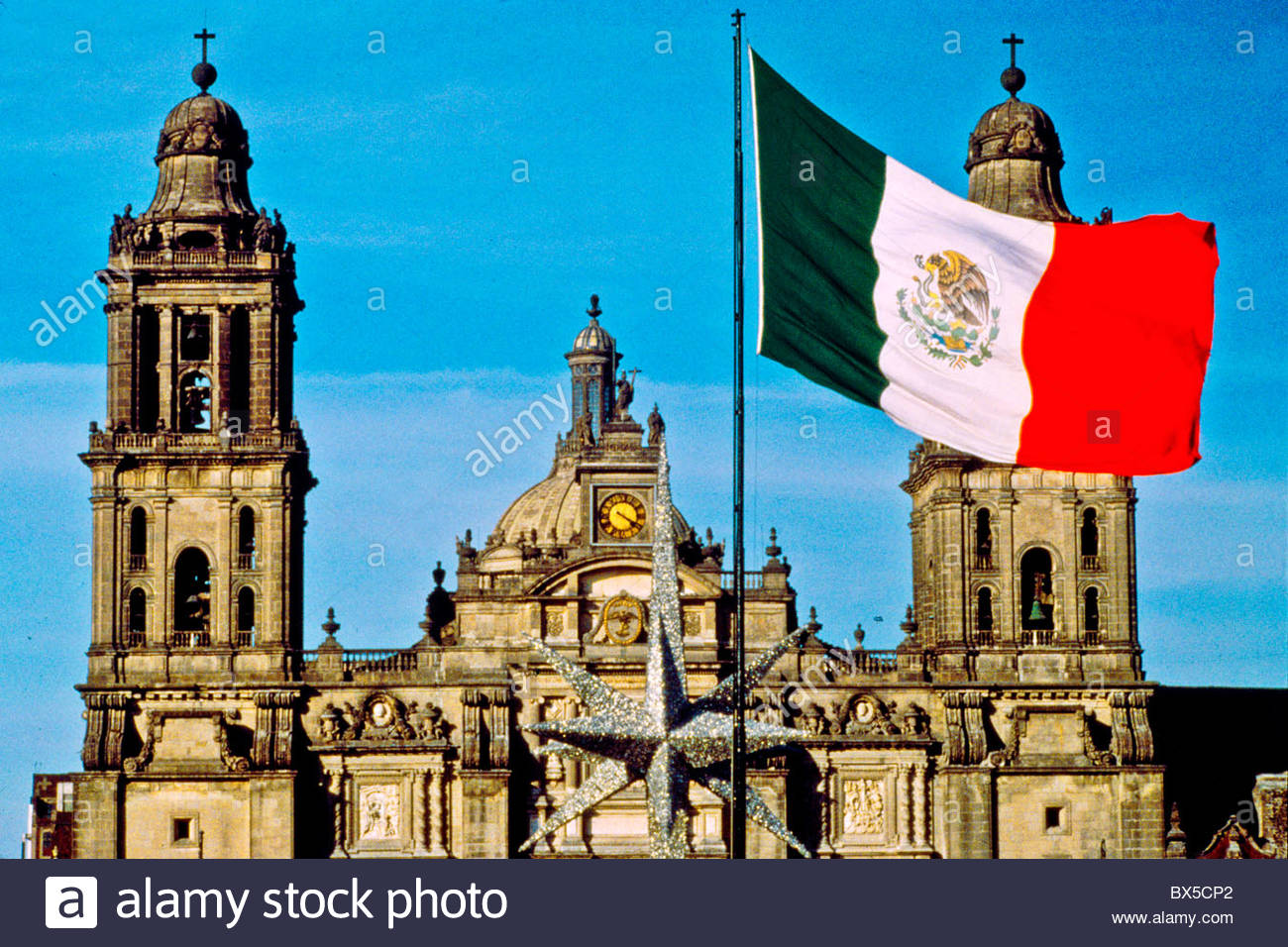 a mexican flag waves outside the cathedral metropoliana in mexico