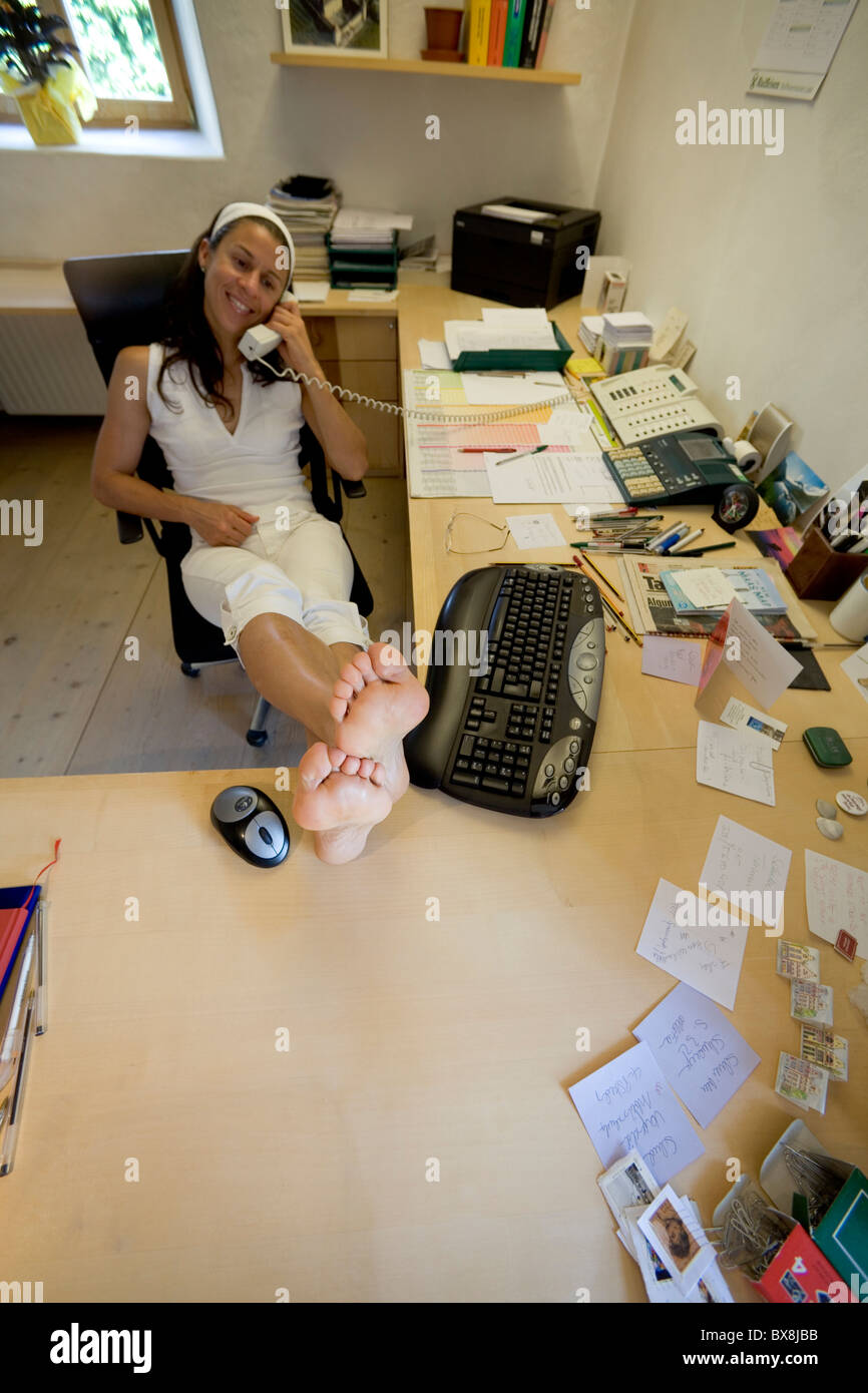 Young Woman With Bare Feet On Desk In Office Using