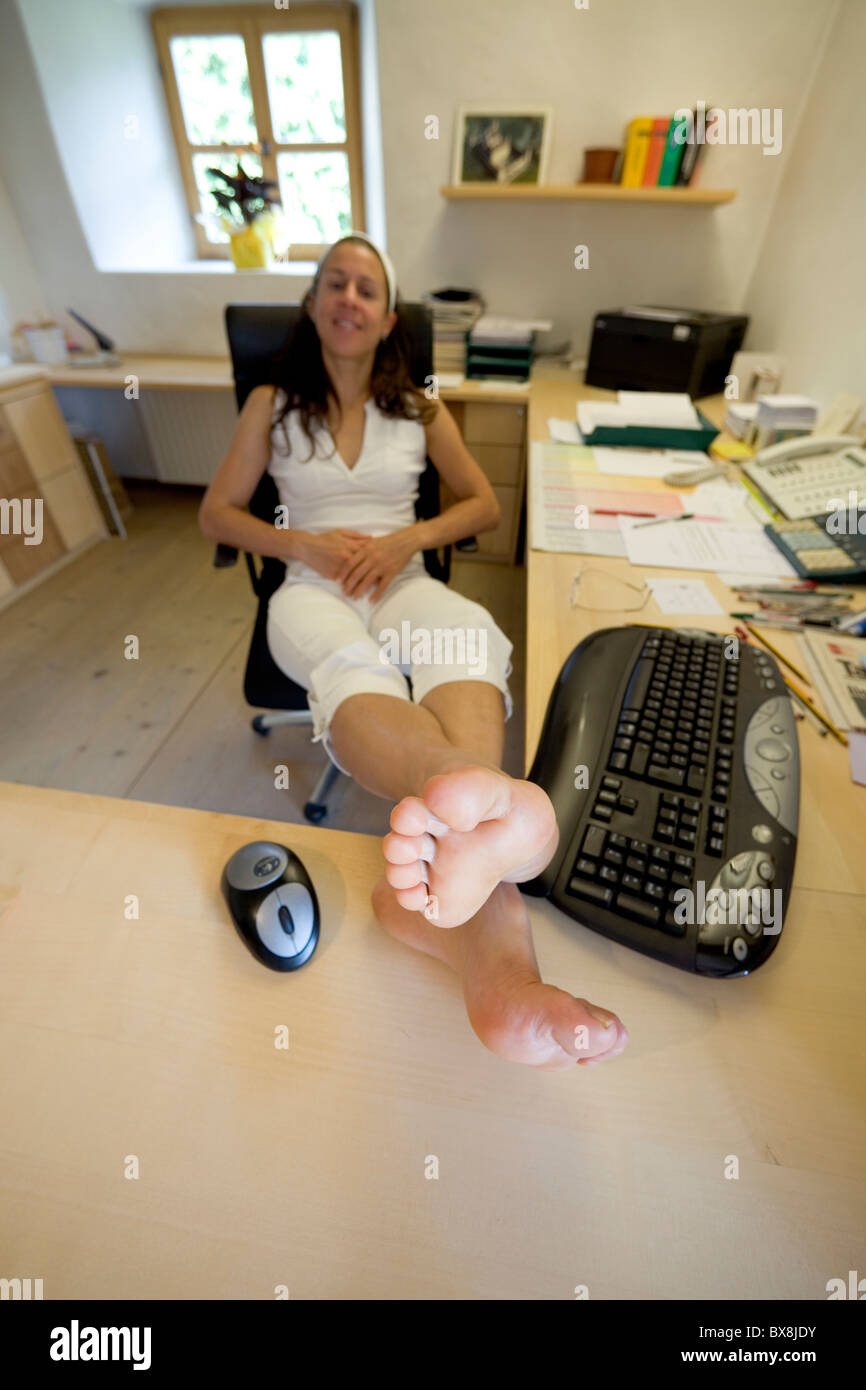 Young Woman With Bare Feet On Desk In Office Stock Photo