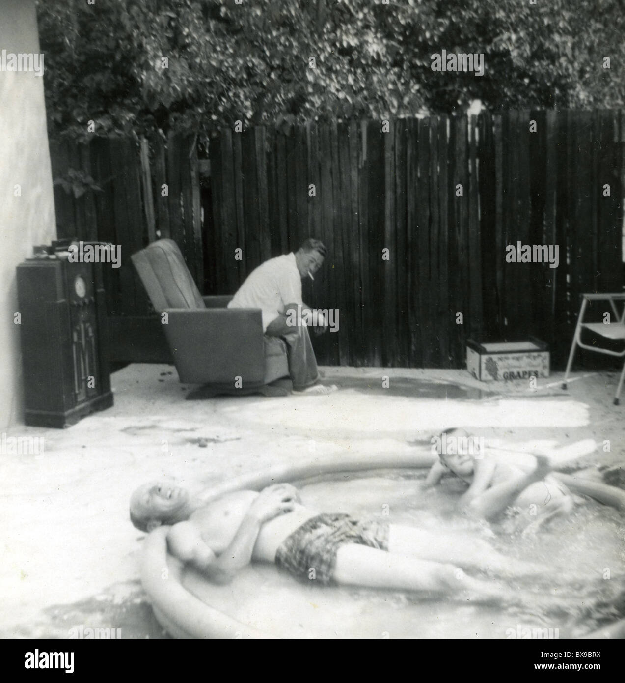 Backyard America Part - 38: Stock Photo - Father And Son Relaxing In Swimming Pool Man Sitting Easy  Chair Tube Radio Backyard America 1950s Portable Pool Hot Day Summer