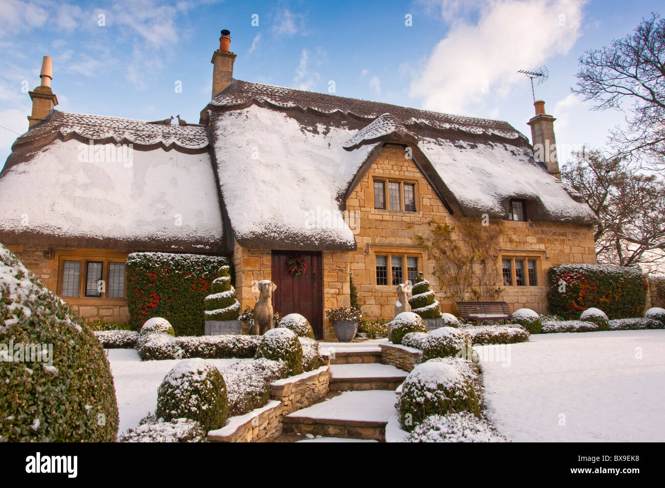 A Thatched Cottage Covered In Snow On The Edge Of The