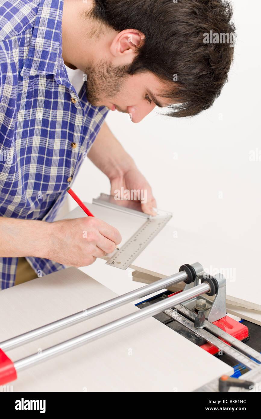Home improvement handyman cut ceramic tile in workshop stock home improvement handyman cut ceramic tile in workshop doublecrazyfo Gallery