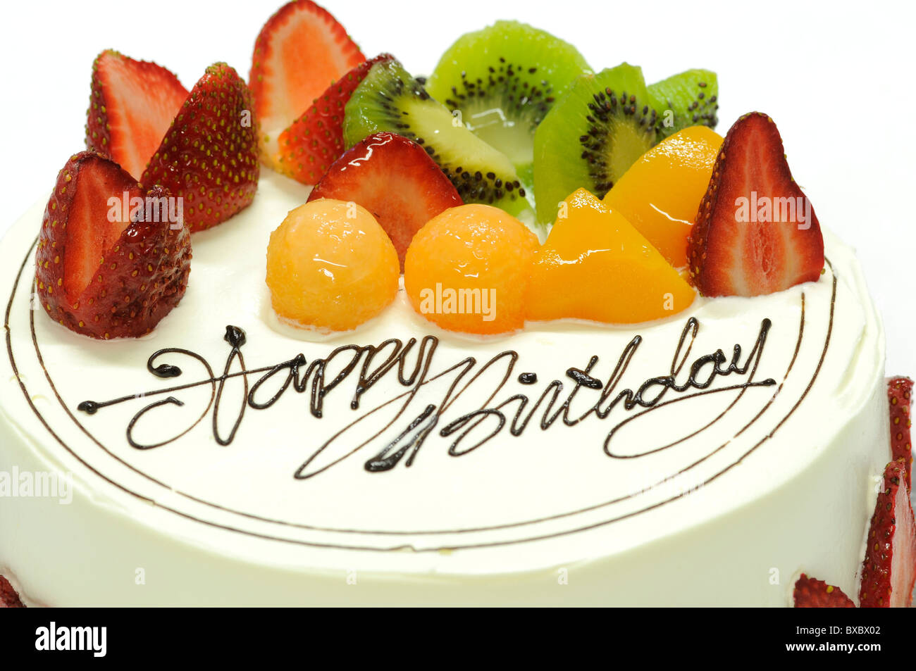 Tasty colorful fruit cake with happy birthday on it Stock Photo