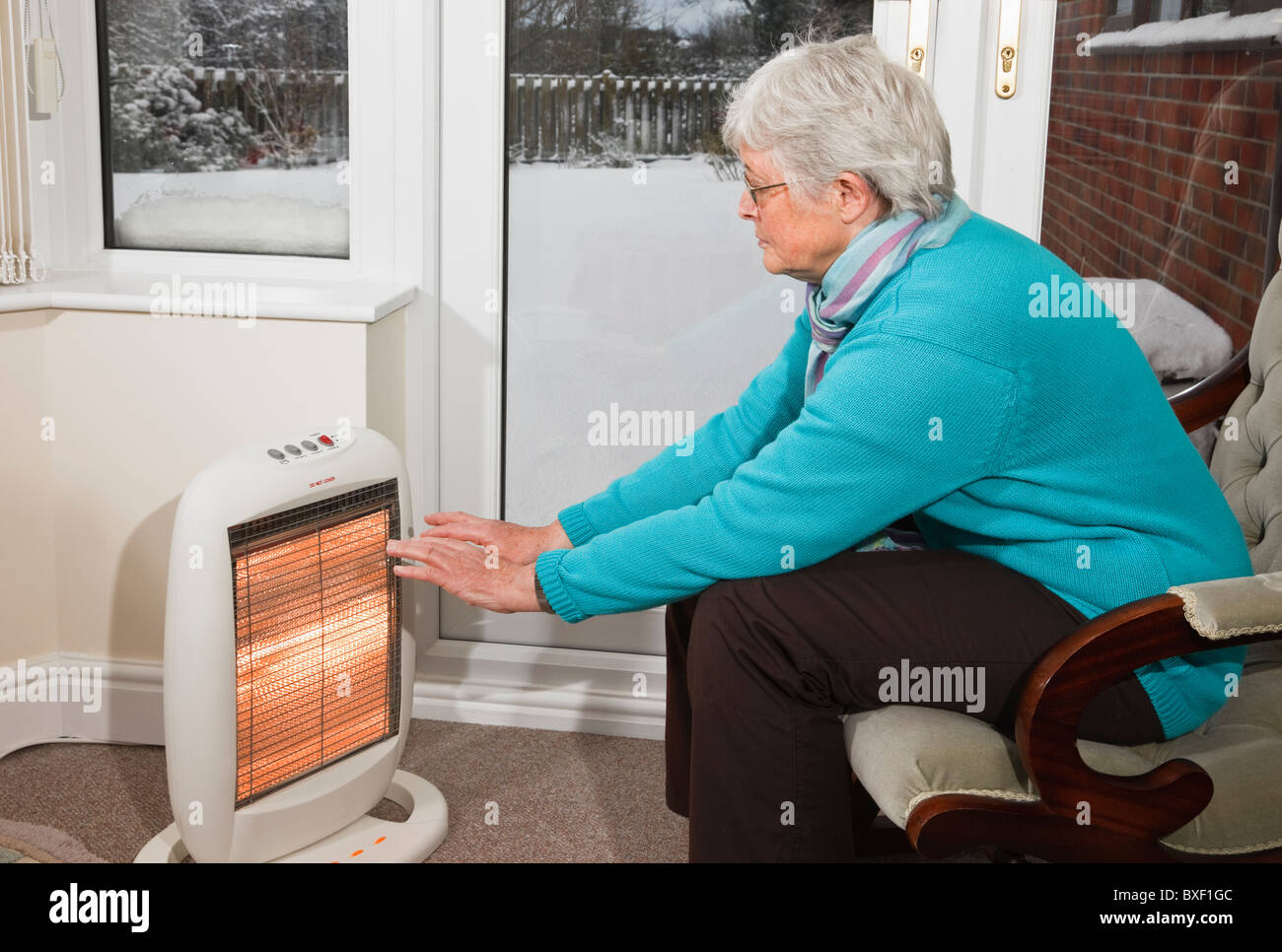 Uk senior woman trying to keep warm indoors sat in front for Warm cheap places to live