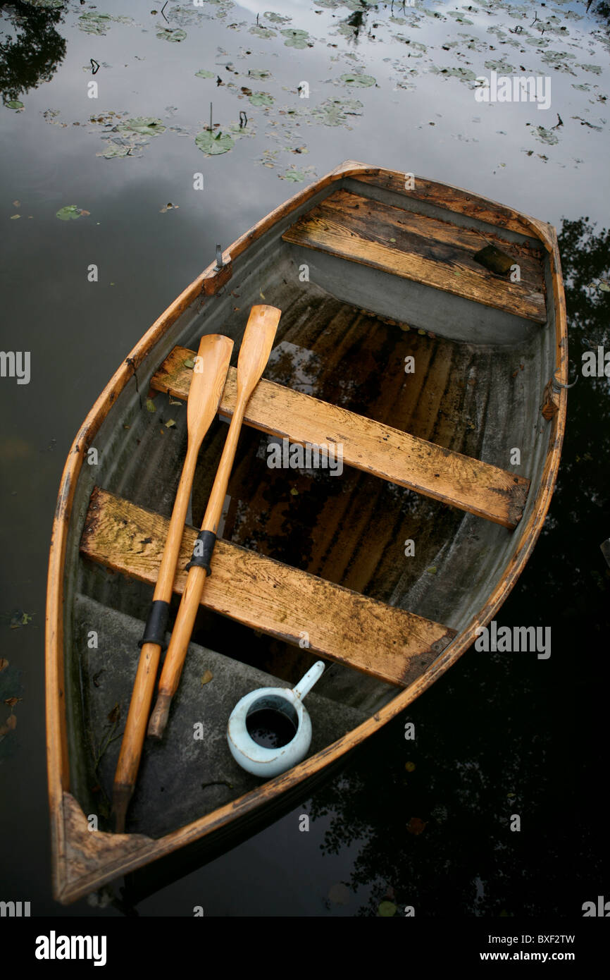 An Old Weather Beaten Wooden Row Boat With Oars And Water Jug View From Above