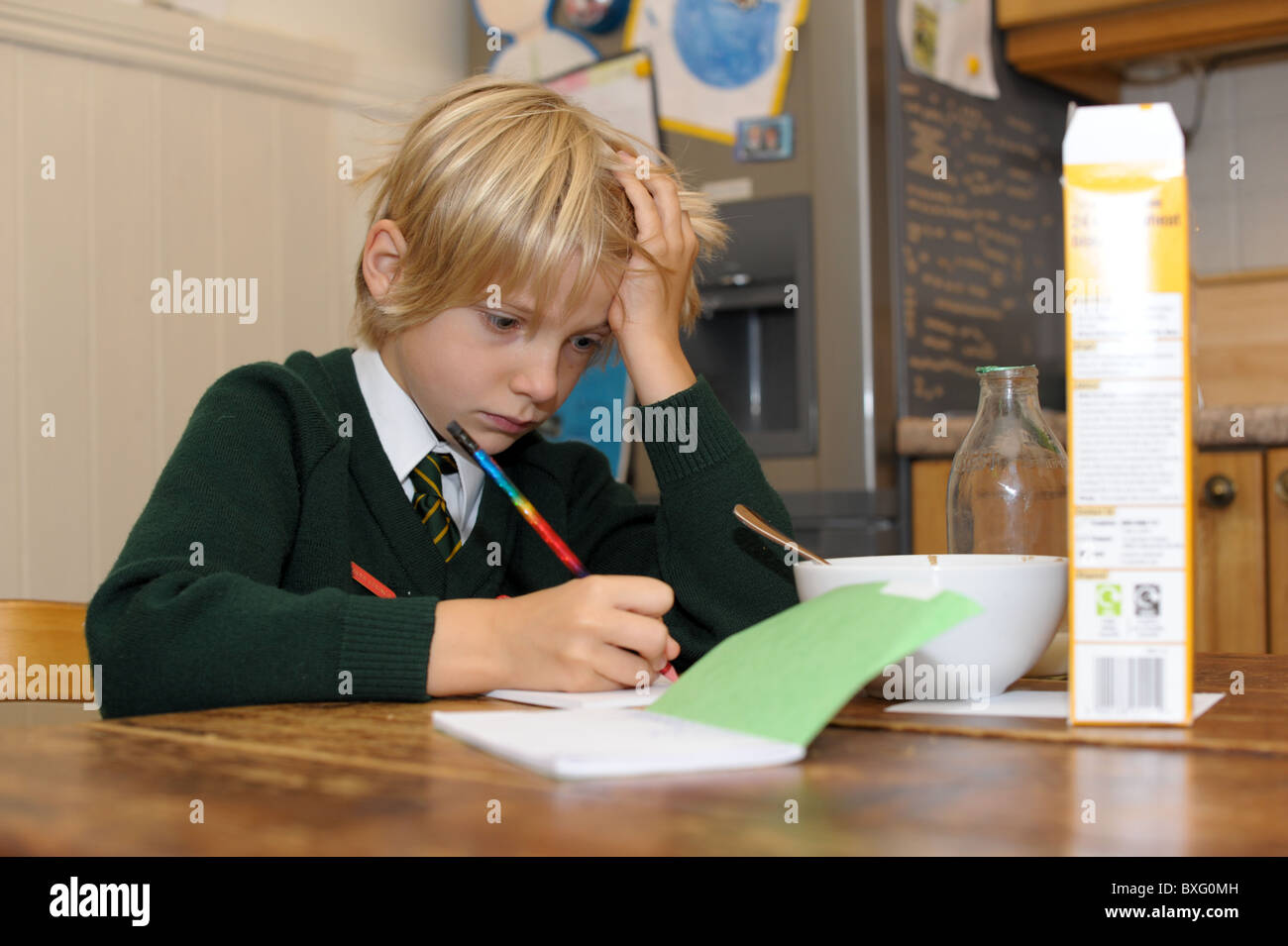young boy in a green school uniform concentrates on his homework