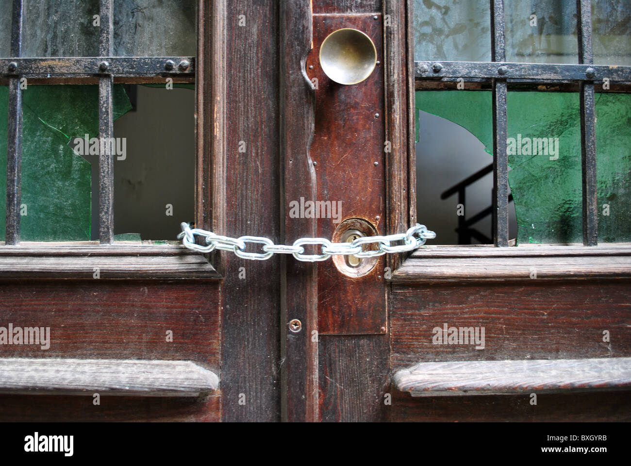 old wooden door with lock and security chain broken glass Stock ...