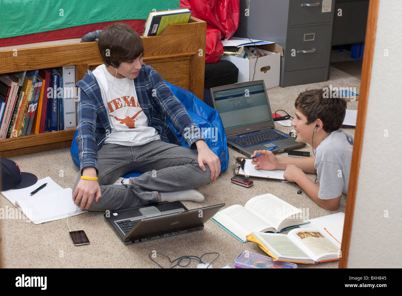 teen boys in bedroom with laptop computer and textbooks