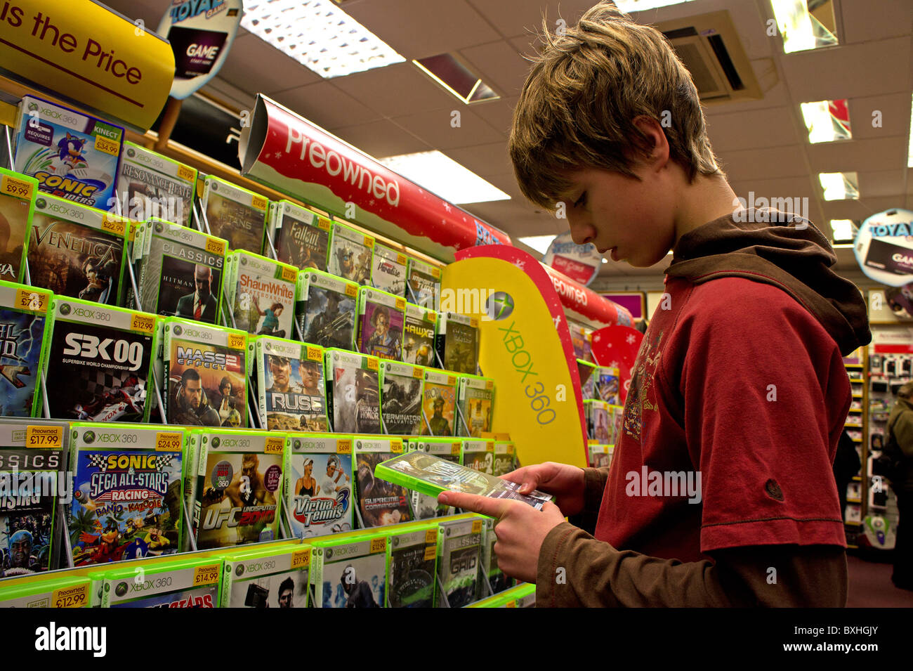 A teenage boy looking at computer games in a Game shop  UK. A teenage boy looking at computer games in a Game shop  UK Stock