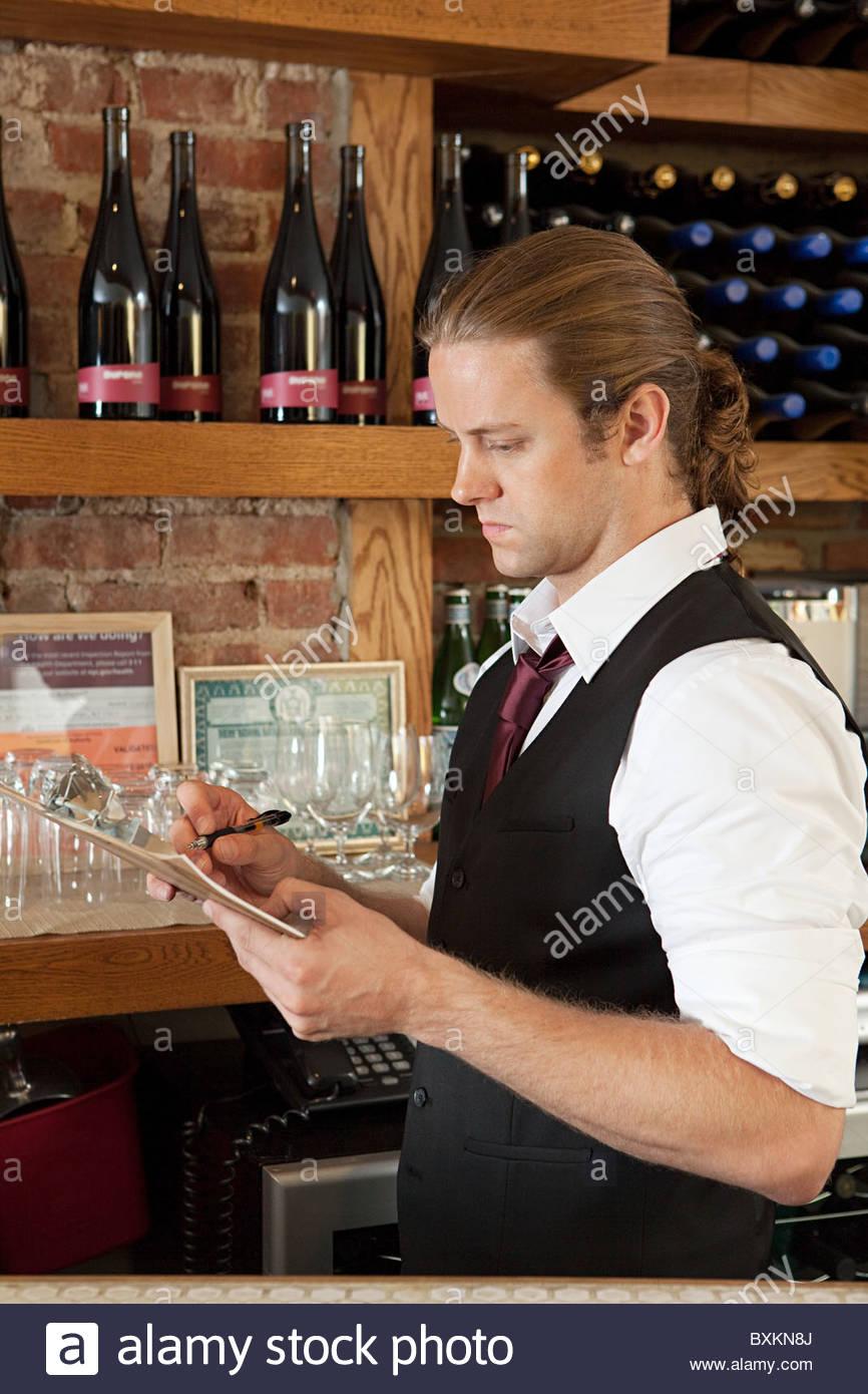 bar manager looking at paperwork stock photo royalty image bar manager looking at paperwork