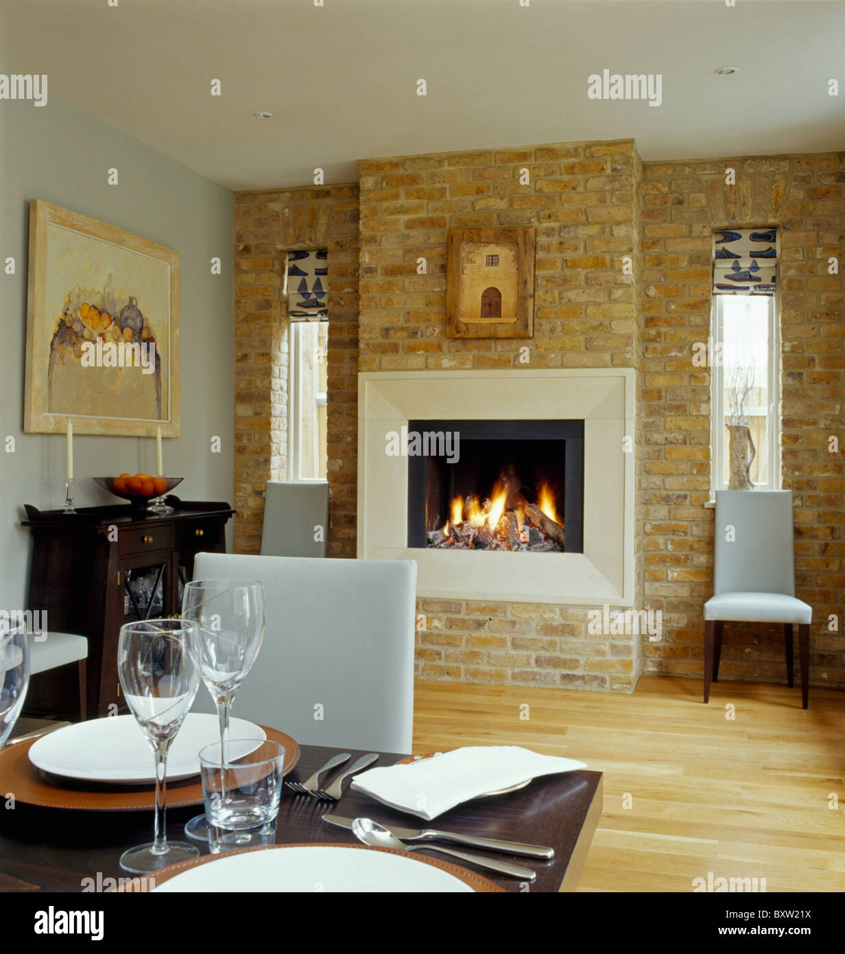 Lighted Fire In Fireplace Exposed Brick Wall Modern Dining Room With White Leather Chairs And Wooden Flooring