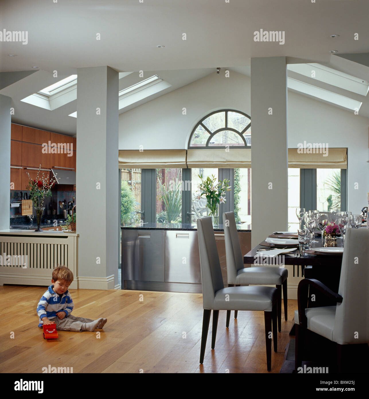 Small Boy Sitting On Wooden Floor Of Modern Kitchen Dining Room Extension