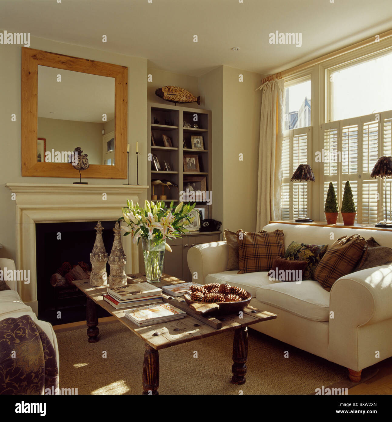 Brown Cushions On Cream Sofa Below Window With Cream Plantation Shutters In  Living Room With Wood Framed Mirror Above Fireplace