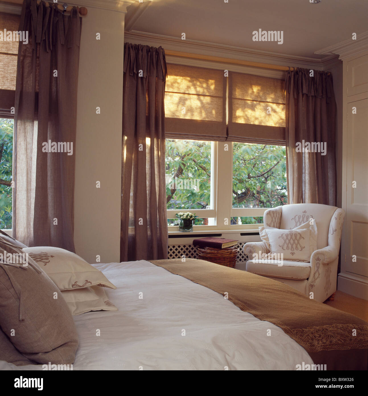 Cream Linen Blinds And Brown Voile Curtains On Windows In