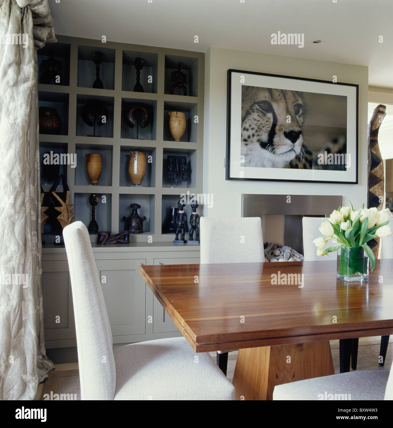 Large Picture Above Fireplace In Cream Dining Room With Cube Alcove Shelving And Chairs At Plain Wood Table
