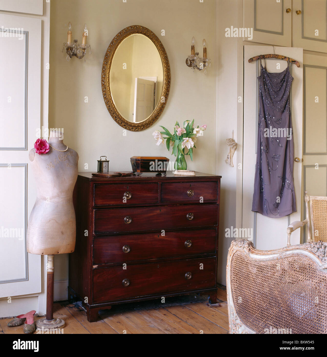 Oval Mirror Above Antique Chest Of Drawers In Townhouse Bedroom With Stock Photo Royalty Free