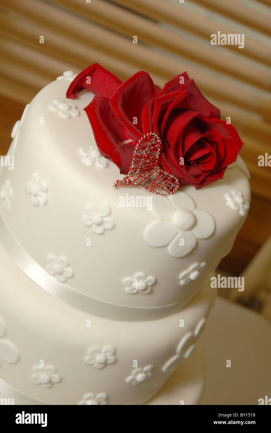 General View Of A White Round Wedding Cake With Real Red Rose Topper And Heart Mad Wire At Reception