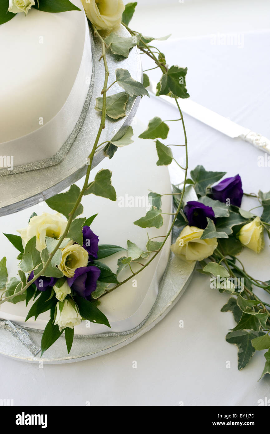 Two Tier White Wedding Cake Draped In Purple And Cream Flowers With Ivy