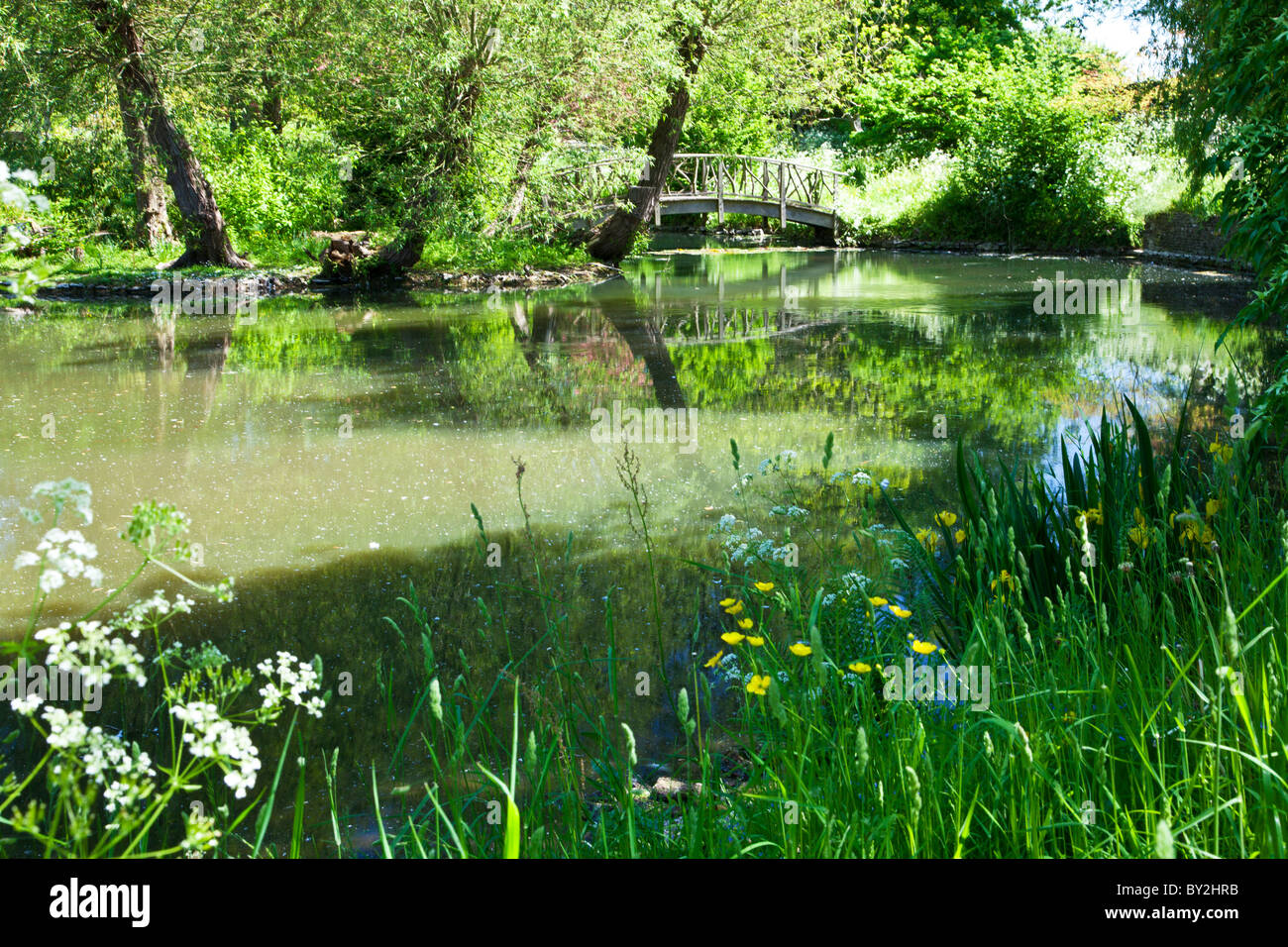 A large ornamental pond or small lake with a rustic wooden for English garden pool