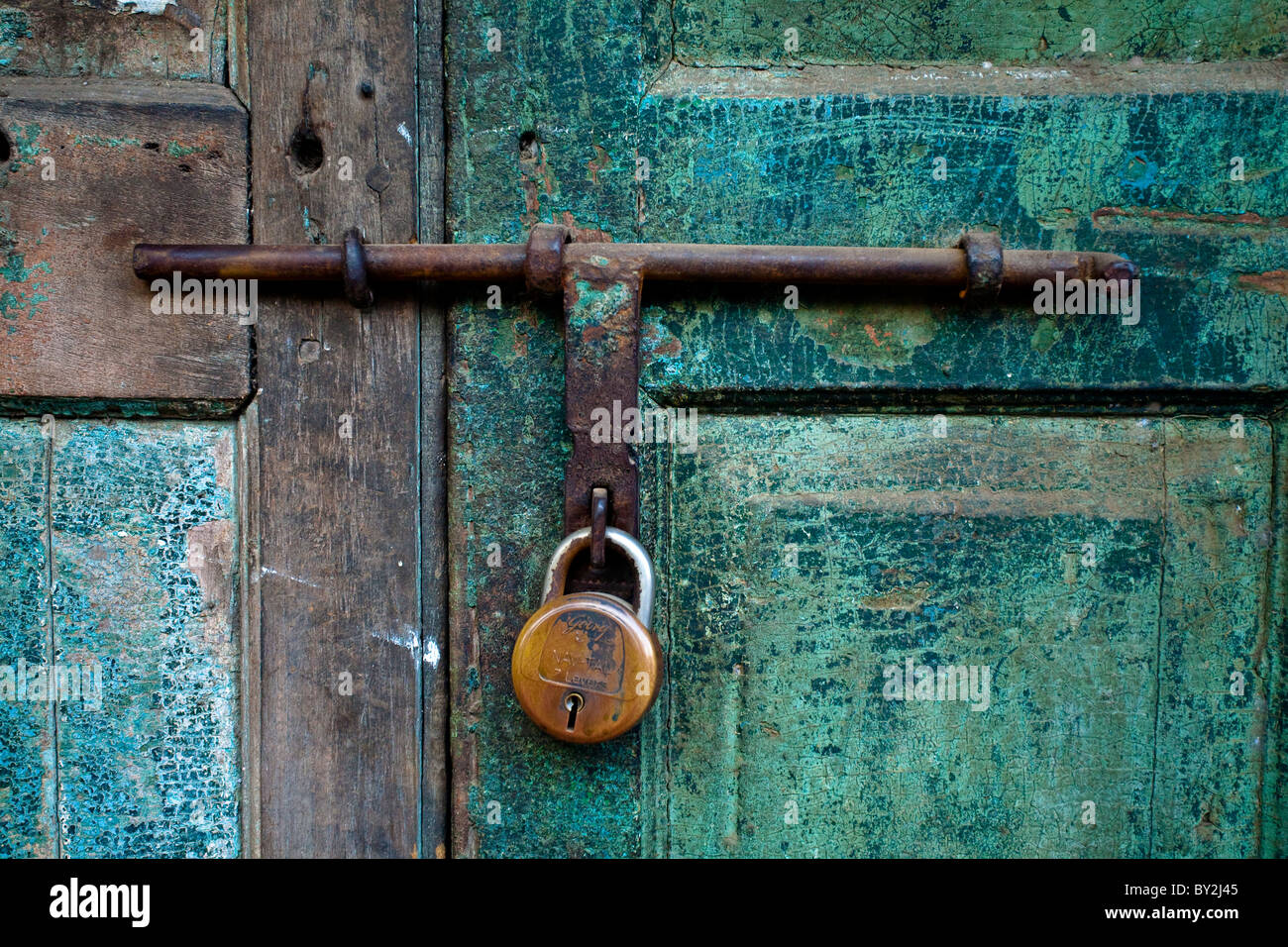 A Close Up Photo Of A Brass Lock On An Old Blue Green Shop