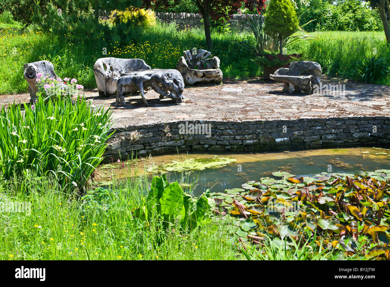 an unusual set of wooden garden furniture made out of driftwood on a terrace by a pond in an english country garden in summer