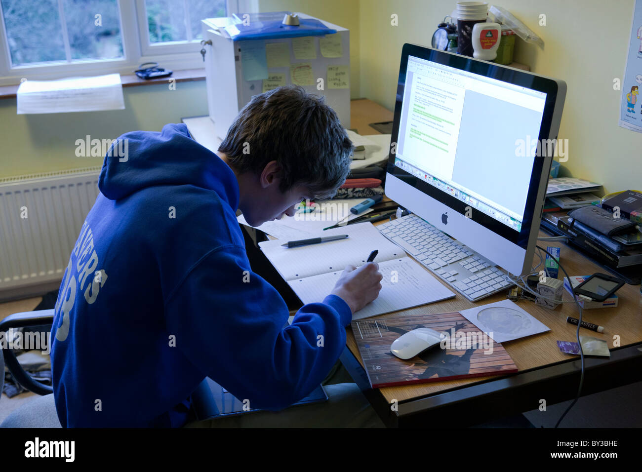 Stock Photo   Student Writing In His Bedroom With A Messy Desk And An Imac