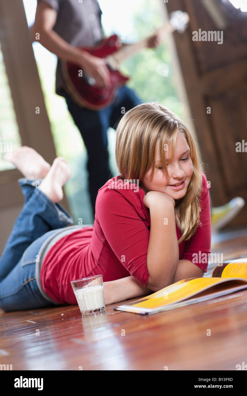 USA, Utah, Girl (10-11) Reading Magazine While Man In The
