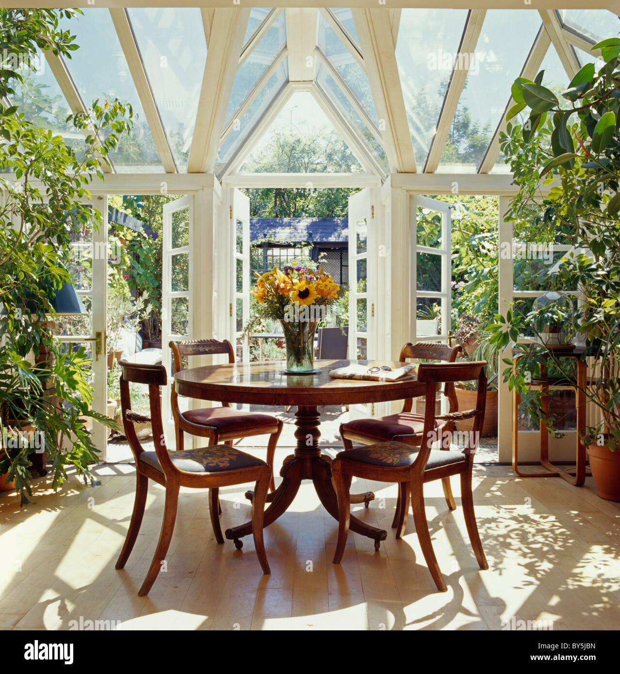 Antique Circular Table And Chairs In Sunny Conservatory Dining Room With Doors Open To Garden