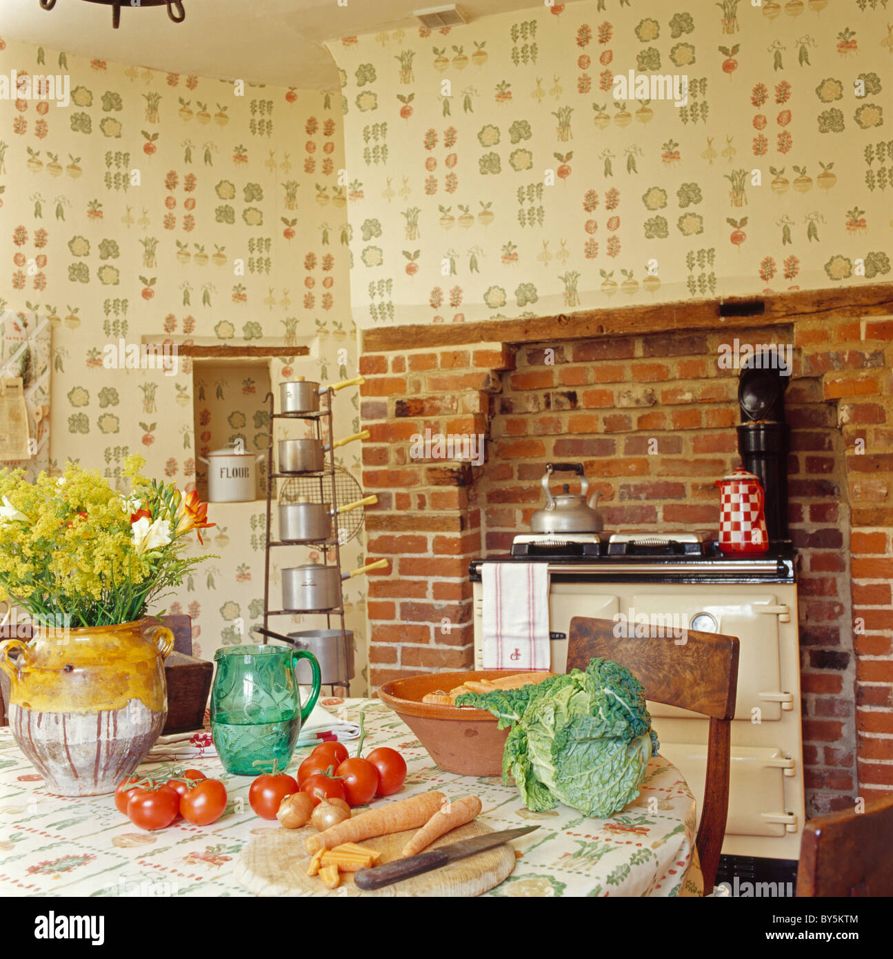 Stock Photo   Vegetables On Table In Country Kitchen With Cream Aga Oven  And Vegetable Patterned Wallpaper
