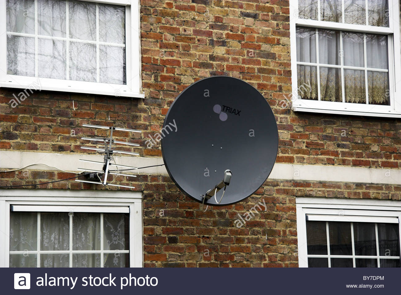 a television satellite dish on the side of apartments in london