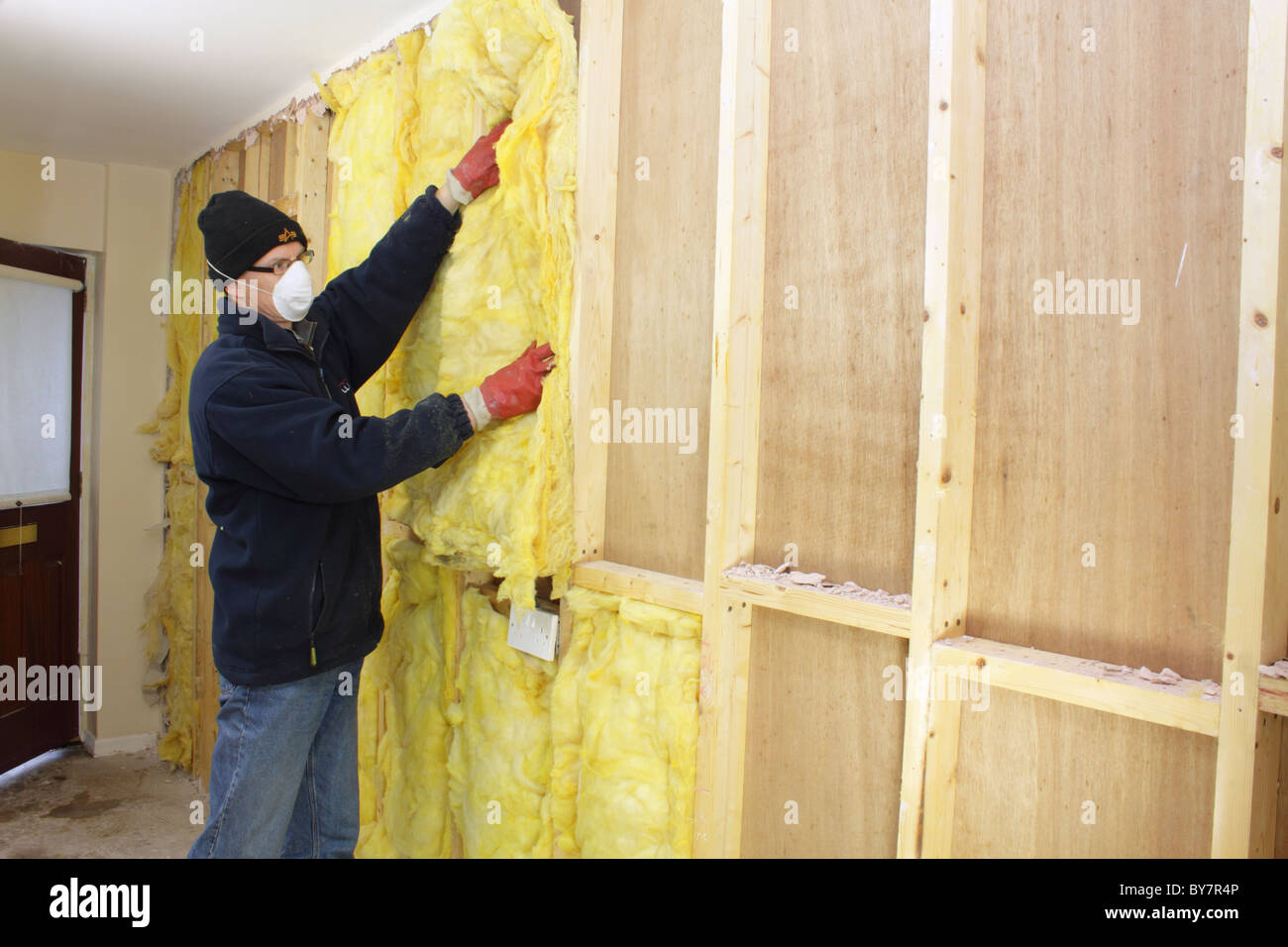 Workman installing rockwool thermal insulation in cavity for Mineral wool wall insulation