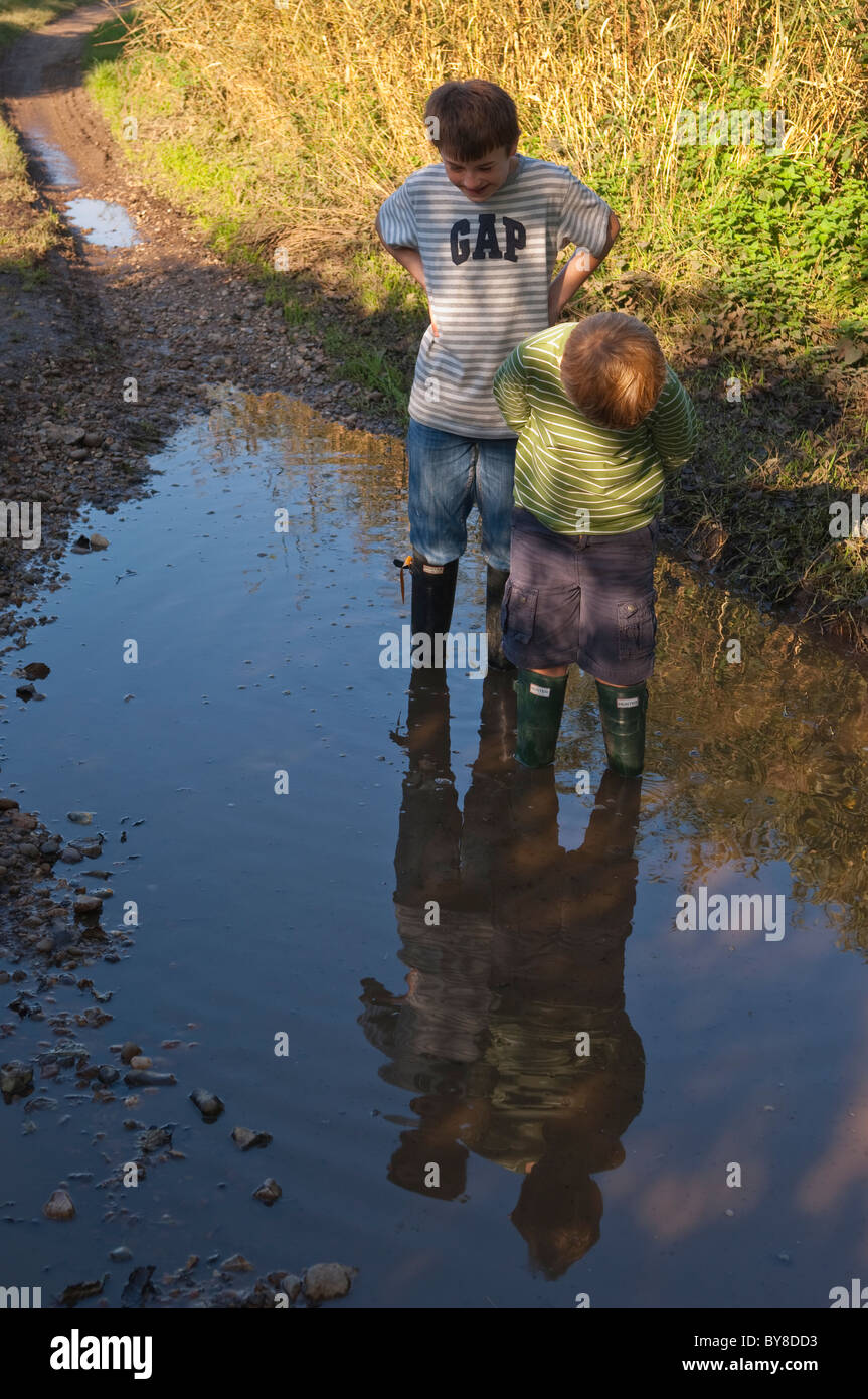 Two Model Released Boys 7 And 11 Stand In A Puddle With Hunter  # Modele Banc En Bois