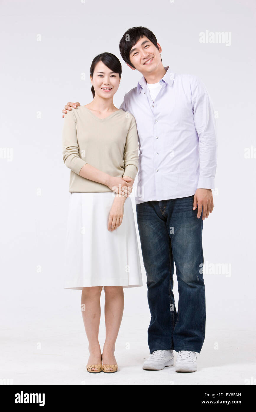 Young couple standing man's arm around woman's shoulder ...