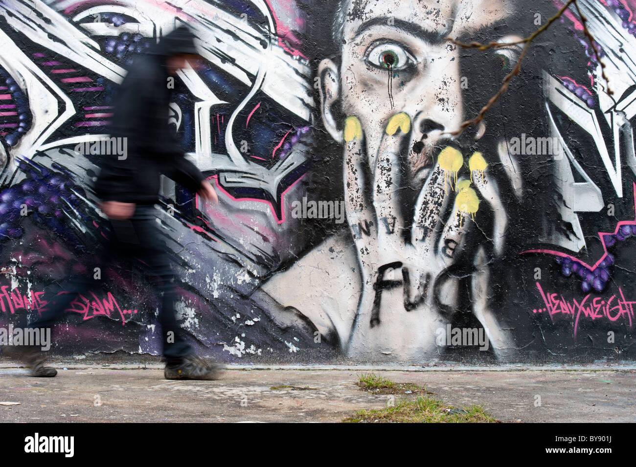 Graffiti wall chelmsford - Stock Photo Man Walking Past Graffiti Wall