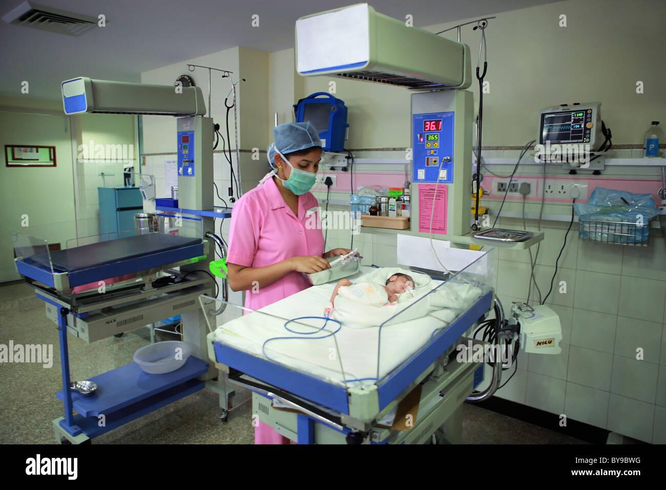 Nurse tending to newborn baby in hospital nursery Photo – Newborn Nursery Nurse