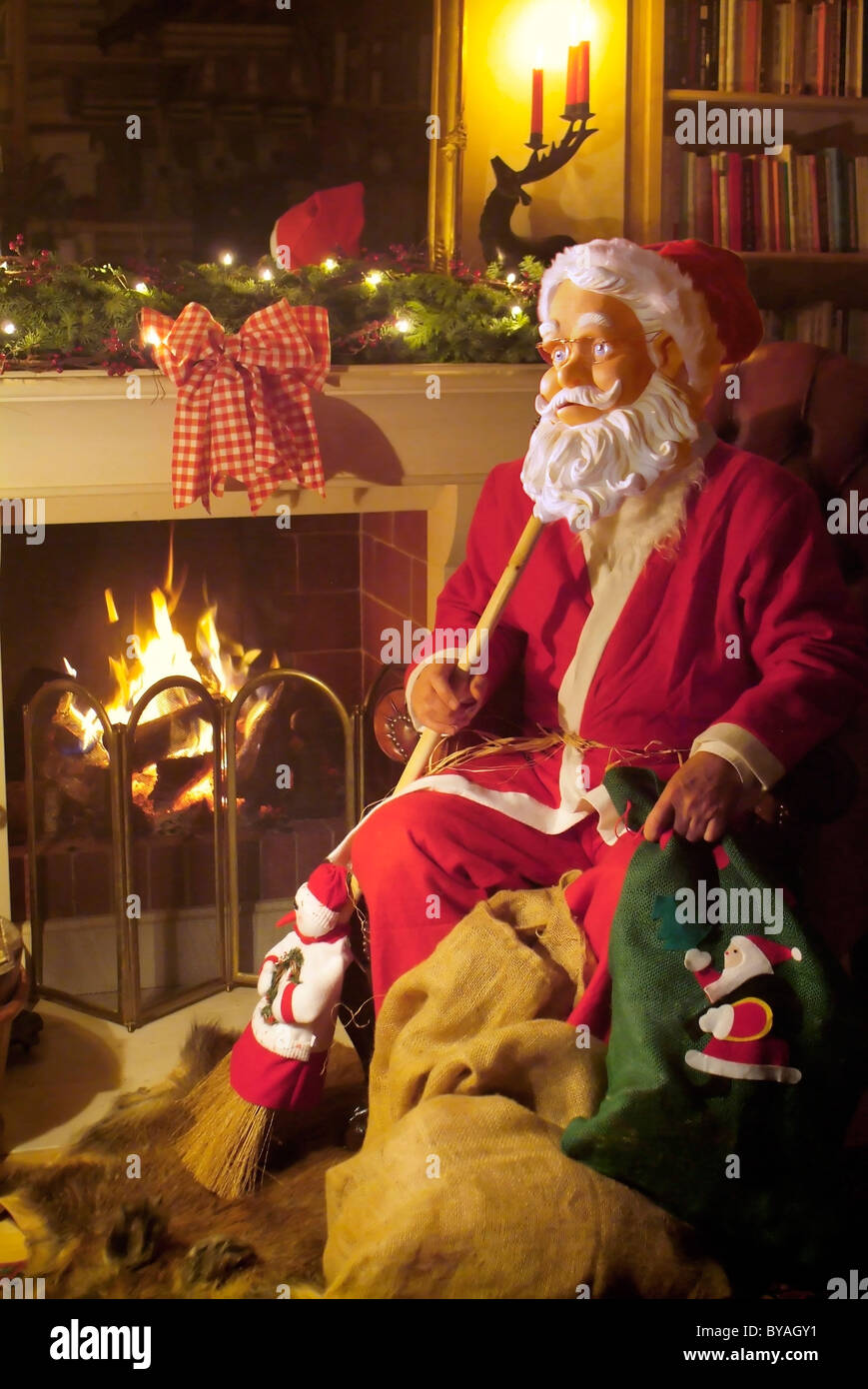 Santa Claus figure sitting in front of fireplace Stock Photo ...