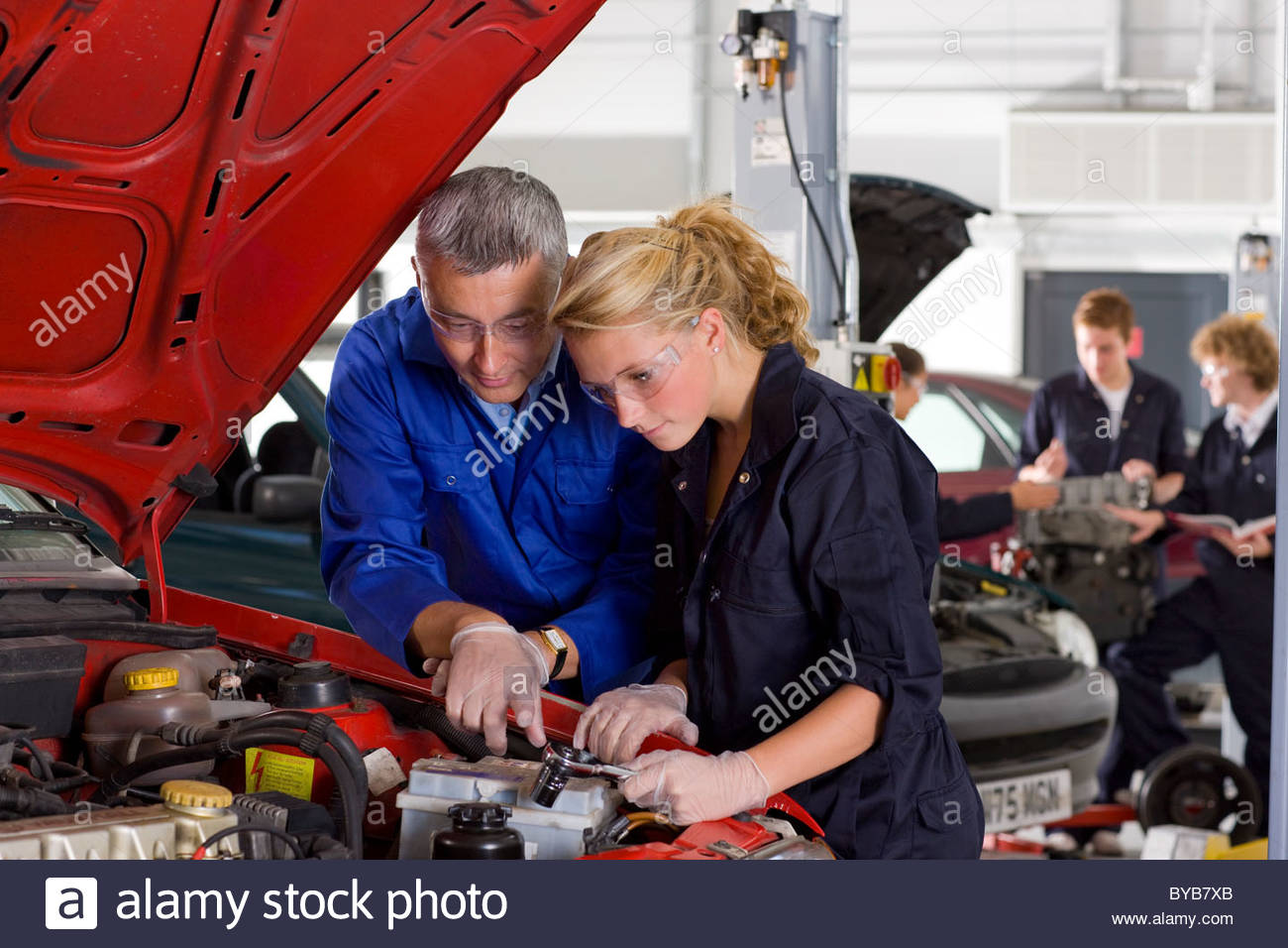 Teacher Helping Student Repair Car In Automotive