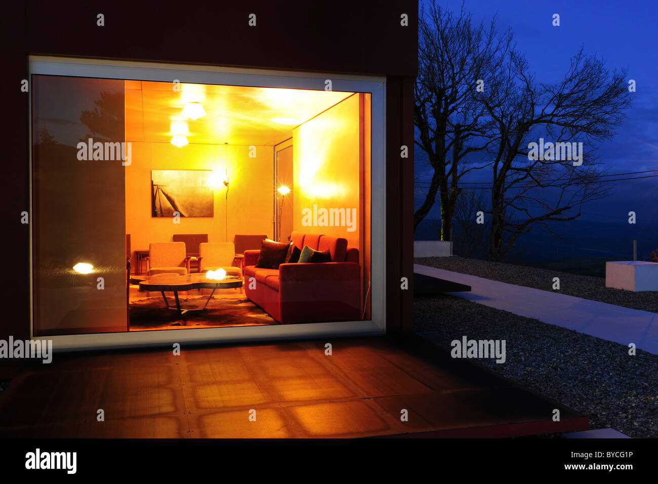 Inside View Of Warm Living Room Through Large Window On A Cold Winter Night At Dusk