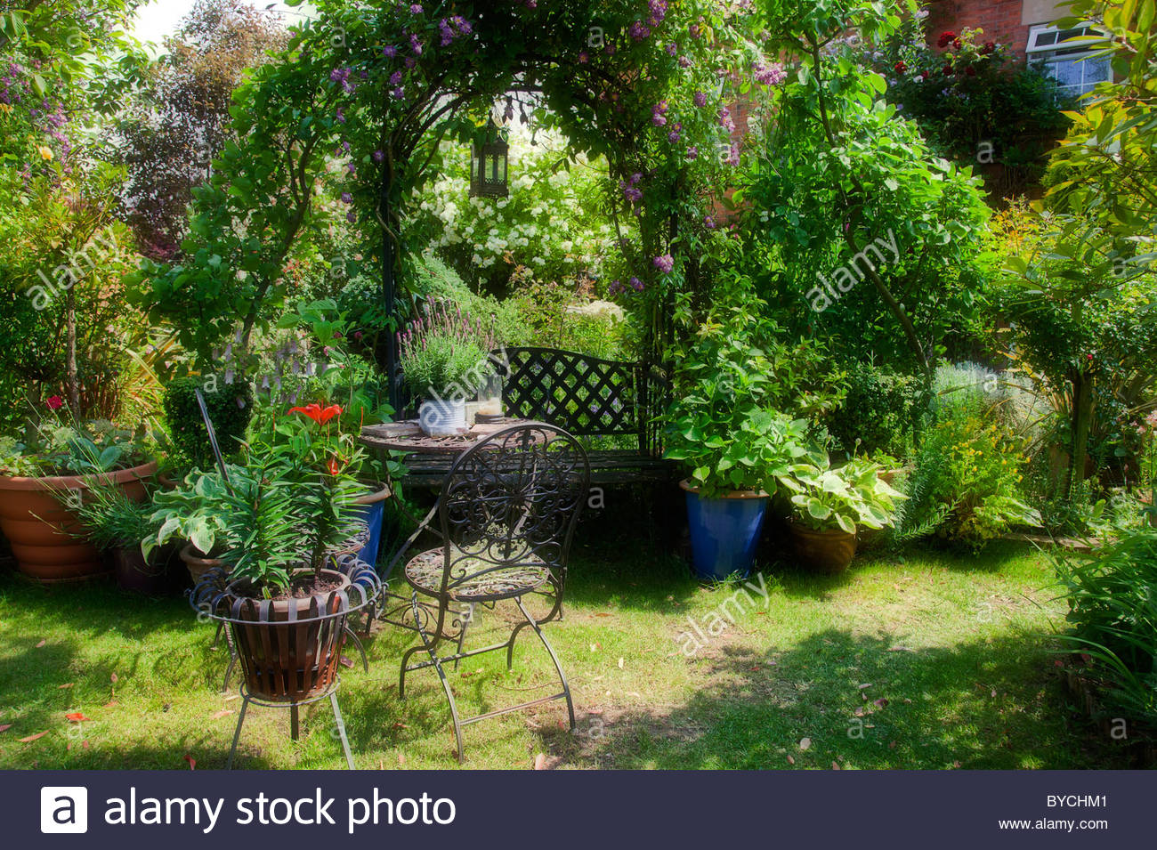 English Country Garden In Summer With Wrought Iron Table