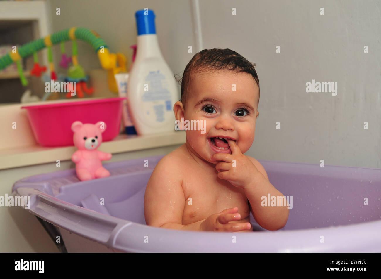 Cute baby bath in a purple bathtub Stock Photo, Royalty Free Image ...