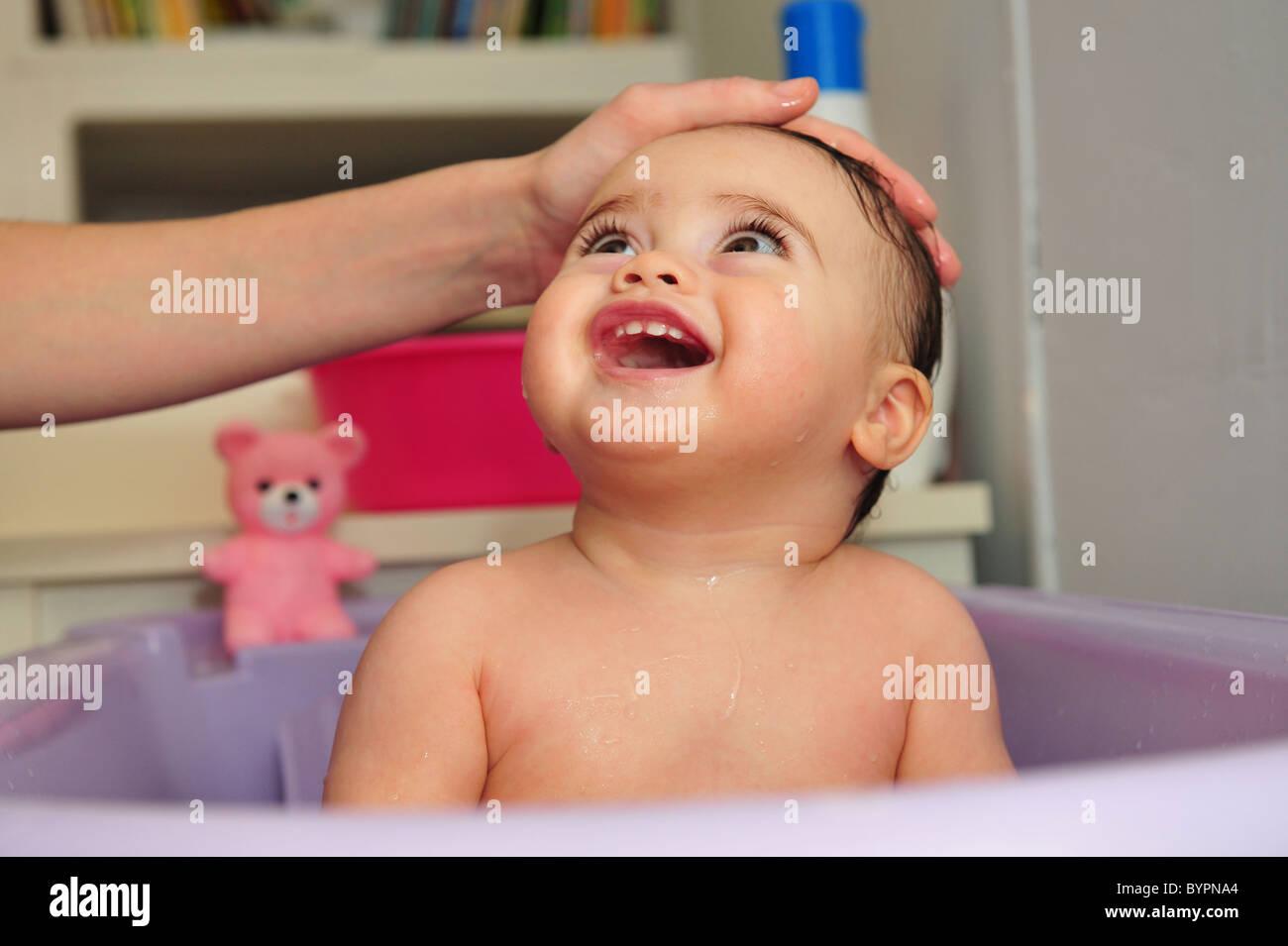 Cute baby bath in a purple bathtub by mother Stock Photo, Royalty ...